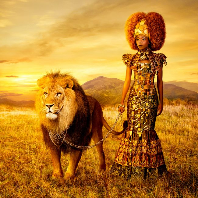 African Woman in Avant Garde Dress Holds a Tame Lion on a Silver Chain in the Savanna