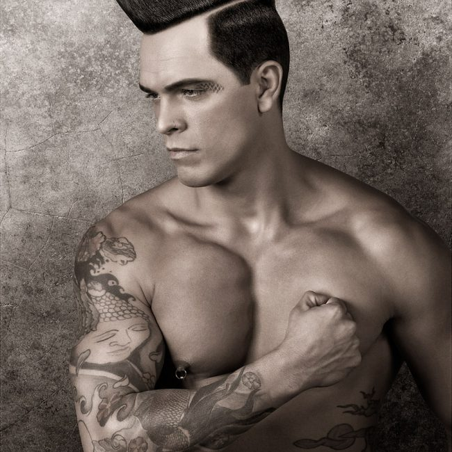 Tattooed Man with Nipple Piercing and Pompadour Hairstyle