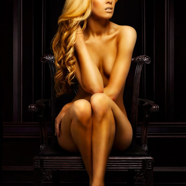 A Nude Woman with Long Golden Hair and Skin Sitting on a Dark Chair with Dark Background