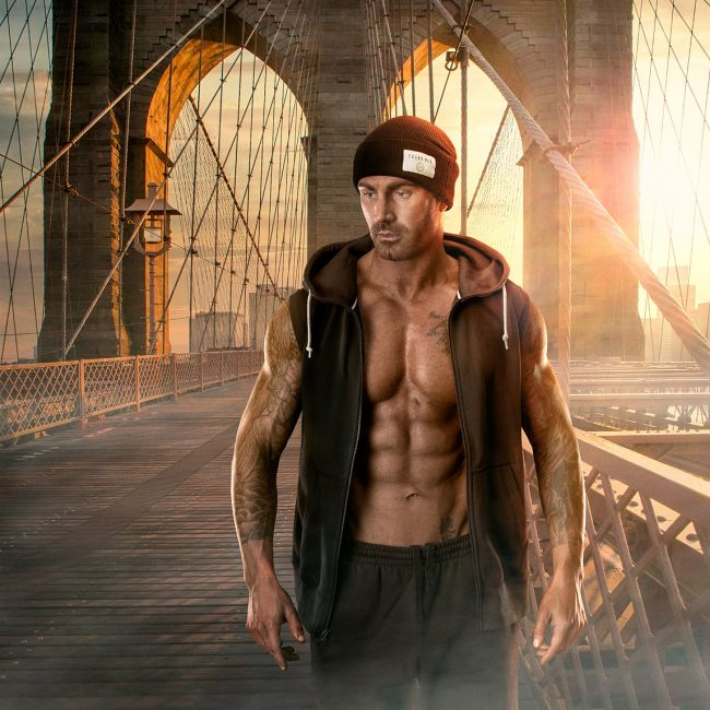 A Muscular Tattooed Man Walks with an Open Vest Revealing Abs on Brooklyn Bridge