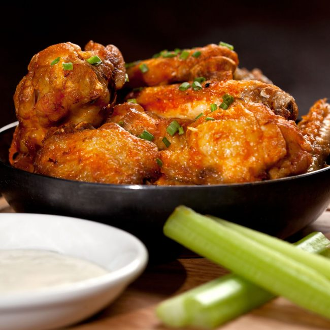 Food Photography of Buffalo Chicken Wings in a Skillet with Celery Sticks and Creamy Dip
