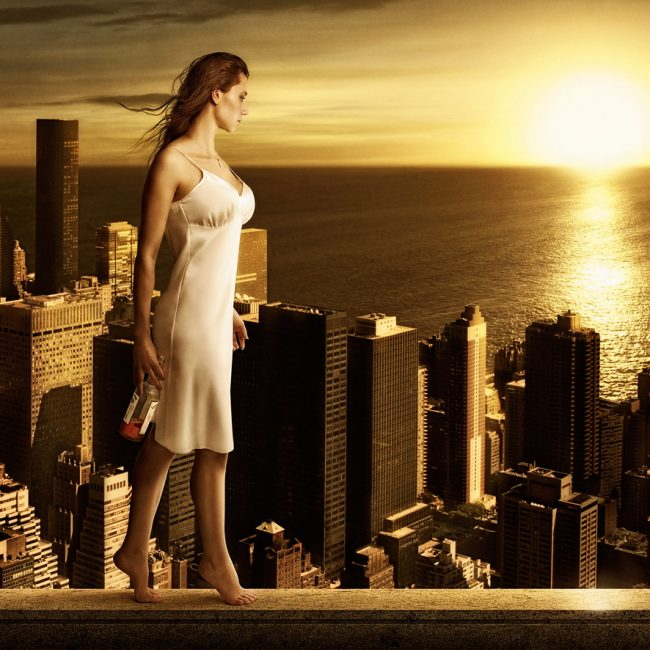A Barefoot Woman in White Dress Tiptoes on the Edge of Skyscraper with Whiskey Bottle in Hand