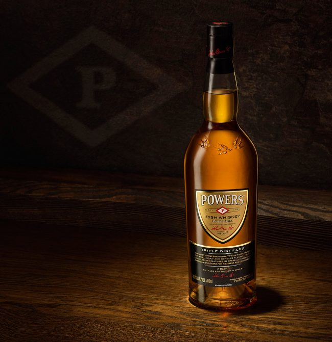 Bottle of Powers Irish Whiskey on Dark Timber Table with Powers Logo in Background